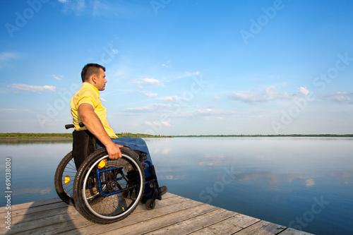 canvas print picture Rollstuhlfahrer schaut auf den See