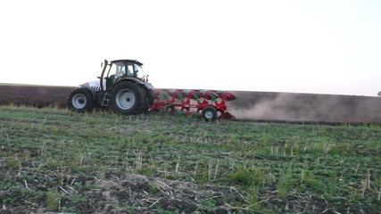 Tractor plowing the black earth plow field at sunset