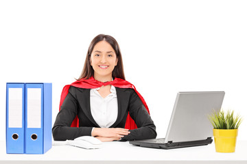 Businesswoman with a red cape sitting at a desk