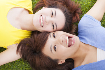 two asian pleasure young woman lying on grass