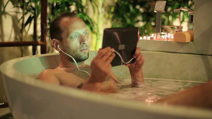 Man watching movie on tablet while lying in bathtub at night