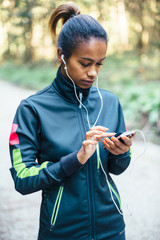 Young woman setting music on phone before running