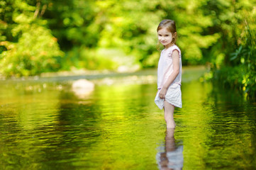 Cute little girl having fun by a river