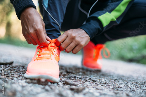 Leinwandbild Motiv Young woman tying laces of running shoes before training