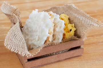 Coconut candy cocada in wooden box with sackcloth