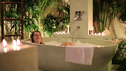 Glamour woman drinking champagne, relaxing in bathtub at night