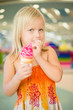 Adorable girl eat fruit ice cream in mall