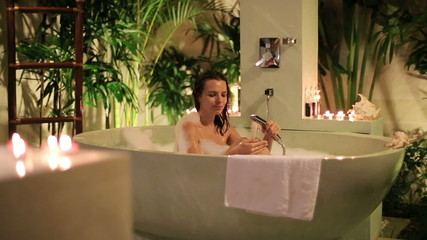 Attractive woman washing her body while lying in bathtub