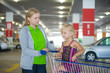 Young mother and adorable daughter in shopping cart on undergrou