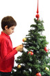 Young boy decorating a Christmas tree