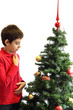 Young boy thinking in front of a Christmas tree