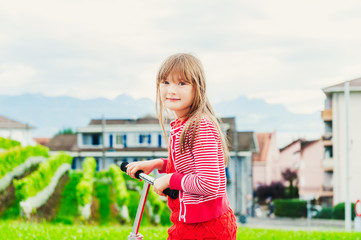 Outdoor portrait of a cute little girl on a scooter