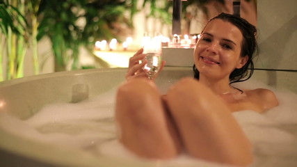 Sexy woman raising toast with champagne while lying in bathtub