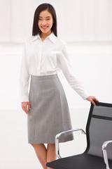 Young asian businesswoman standing near chair