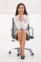 Happy asian businesswoman sitting chair