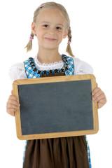 Mädchen im Dirndl hält Tafel mit Textfreiraum