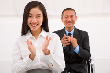 Close-up of smiling businesspeople clapping