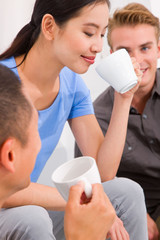 Asian young woman drinking coffee with her friends