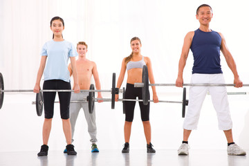 Multiethnic group of people exercising with weightlifting bar in