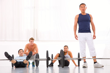 Multiethnic group of people resting after workout in gym