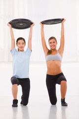Two young woman lifting weight in gym