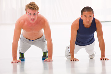 Two young man doing push-ups in gym