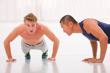 Two young male doing push-ups in gym
