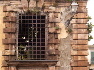 Old window with iron bars and lantern