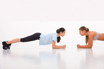 Two happy young woman doing push-ups in gym