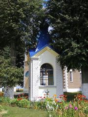 Маленькая колокольня во дворе деревенской православной церкви.