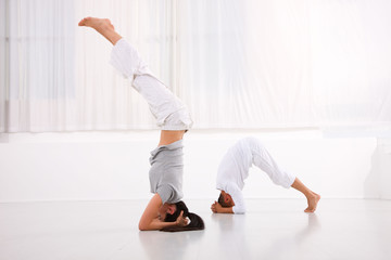 Man and woman practicing yoga in fitness studio