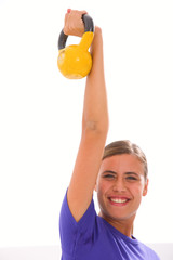 Happy fitness woman lifting kettlebell