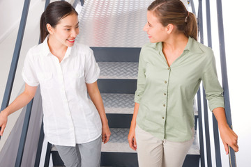 Two smiling young woman standing staircase