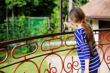 Smiling little girl  painting fence