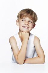 Young boy in vest looking away, studio.