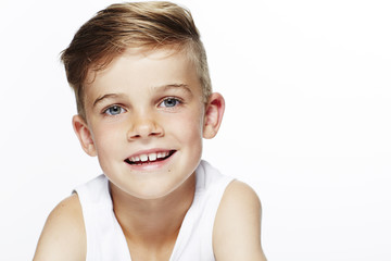 Portrait of young boy in vest, smiling.