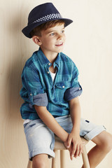 Young boy wearing checked shirt and hat.