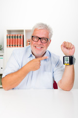 mann zeigt auf blutdruckmessgerät