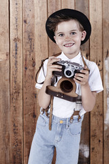 Young boy holding old camera, portrait.