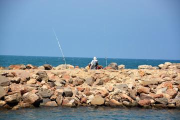 pescador prescando sobre un rompeolas en verano