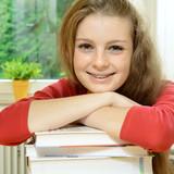 Freundliche Schülerin stützt sich auf Bücher