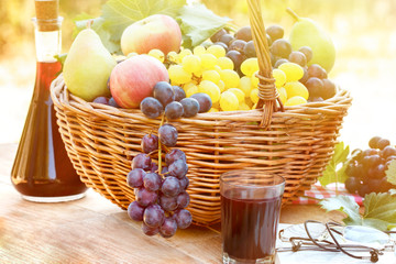 Autumn harvest in wicker basket and red wine