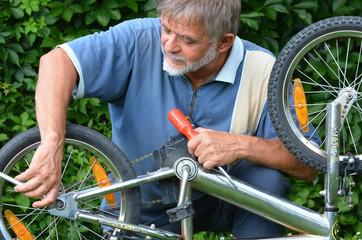 Rentner repariert Fahrrad vom Enkel