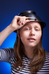 Calm teen girl with a colander on her head
