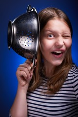Teen girl holding colander and grimacing