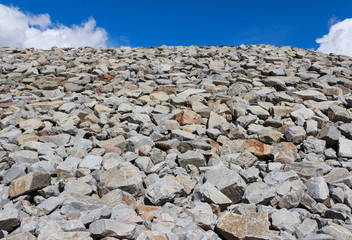 Lots of rocks piled up against a blue sky with some clouds