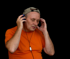 Portrait of mature man listening music with headphones