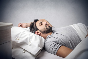 man deeply asleep in his bed