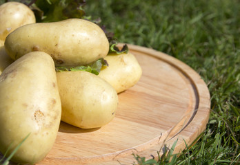 young potatoes on wood tray
