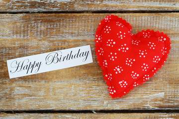 Happy birthday card with red heart on wooden surface